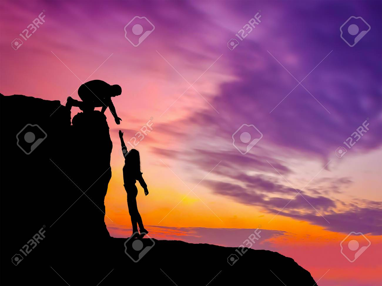 Silhouettes of two people climbing on mountain and helping. - 121212753
