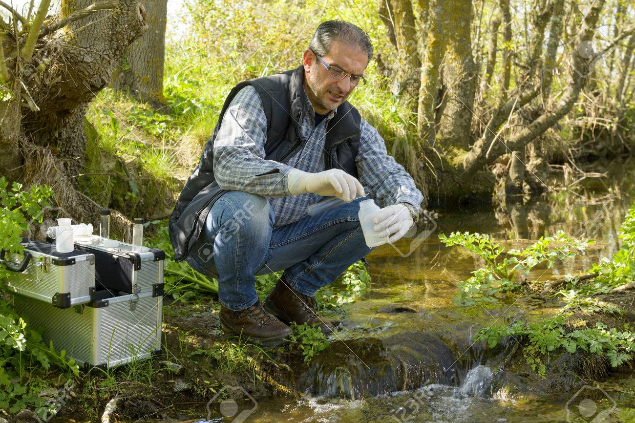 Scientist and biologist hydro-biologist takes water samples for analysis. - 75541508