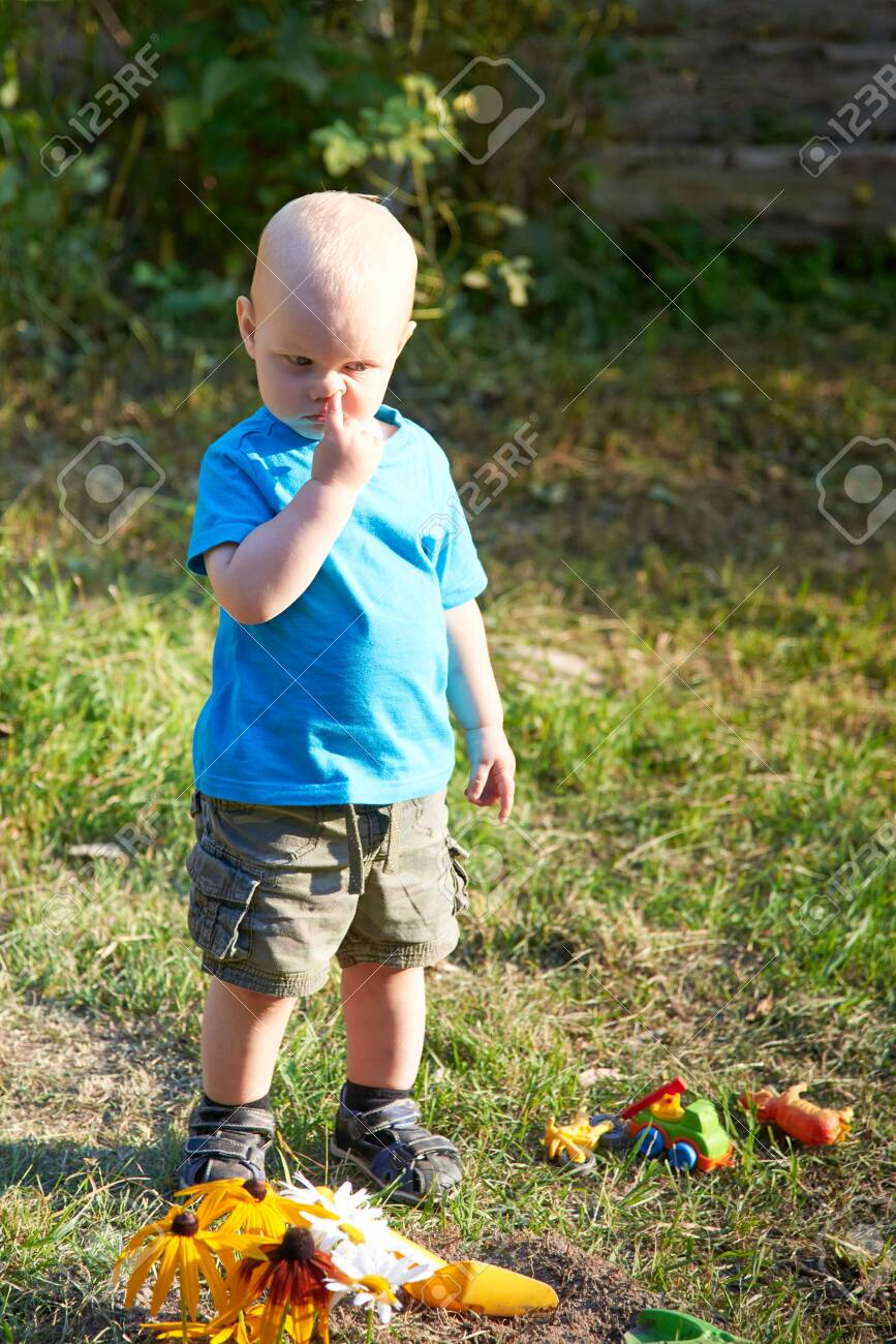 A little boy with a finger in his nose is standing on the grass near his toys on a summer day, the theme of bad children's habits - 131276013