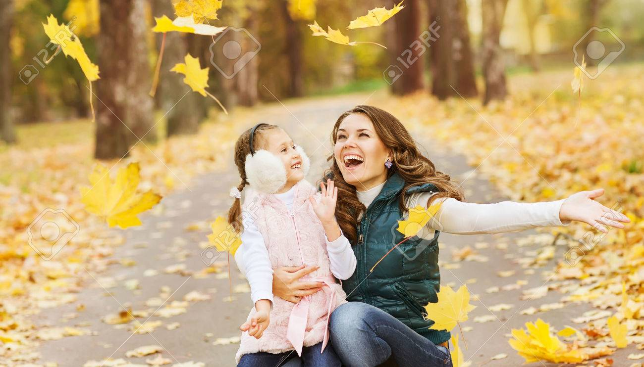 Mother and daughter having fun in the autumn park among the falling leaves. Stock Photo - 24258063