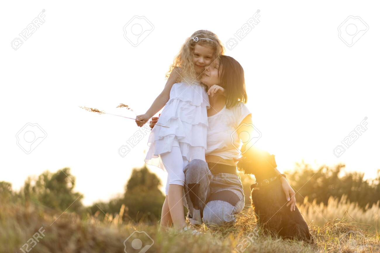 Mother with daughter with dog Miniature Schnauzer plays at sunset - 129390396