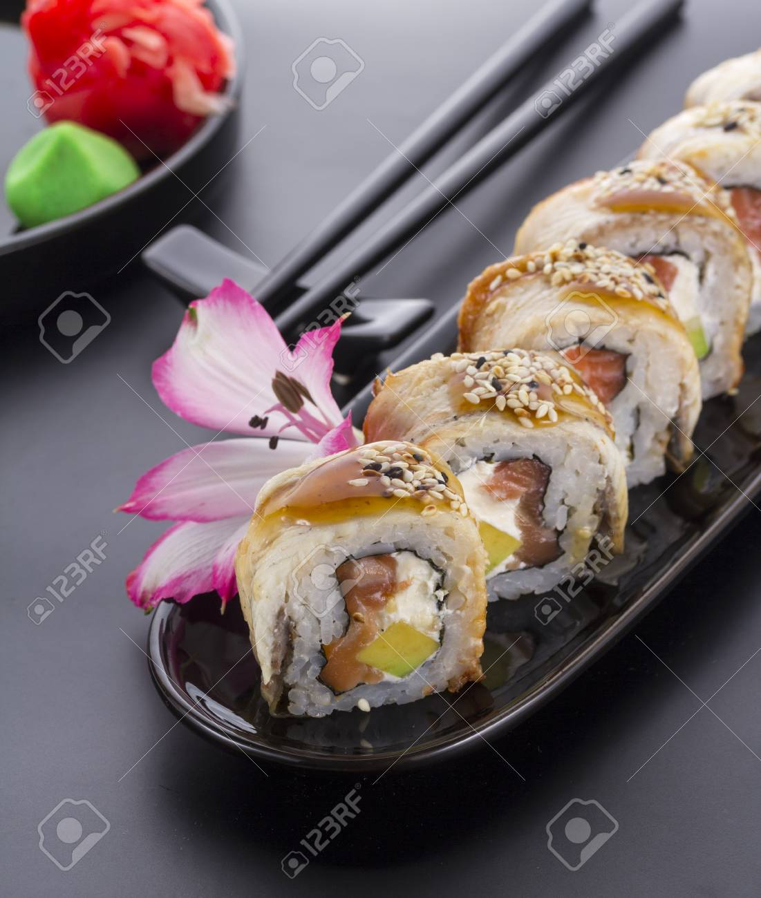 Eel Sushi Roll On A Black Plate With Flower Decoration Stock Photo 53779622