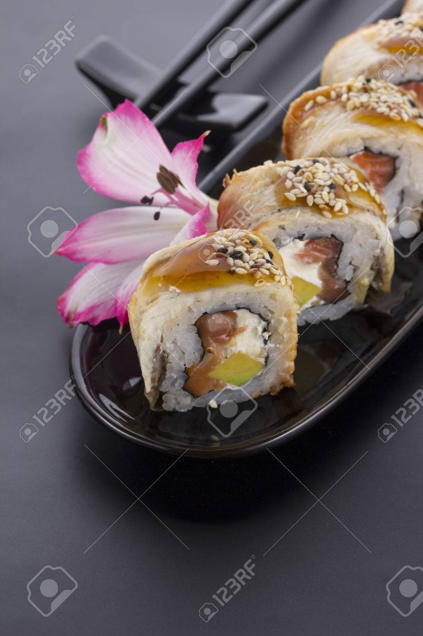 Eel Sushi Roll On A Black Plate With Flower Decoration Stock Photo 53780536