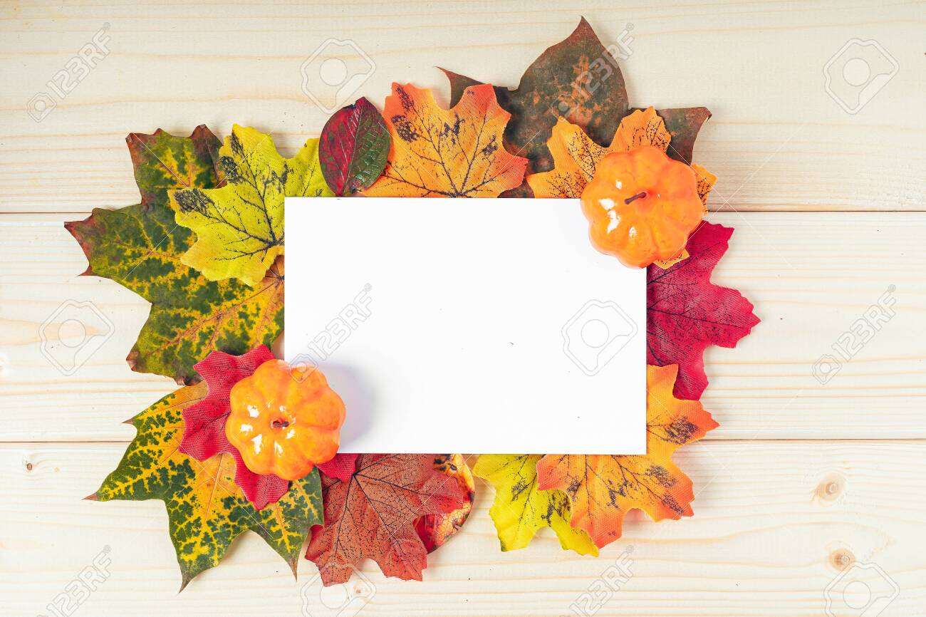 Orange pumpkins, maple leaf, berries and mock up paper blank on wooden background. Hello Fall greeting card, autumn time concept. Flat lay. Copy space. - 155500547