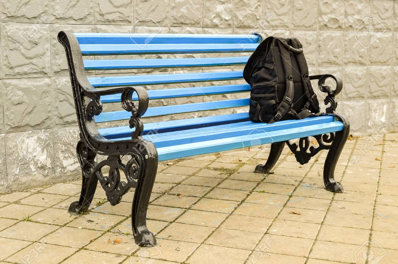 Stock Photo   The Blue Bench In The Park On The Tiled Pavement With A Black  Backpack. No Body