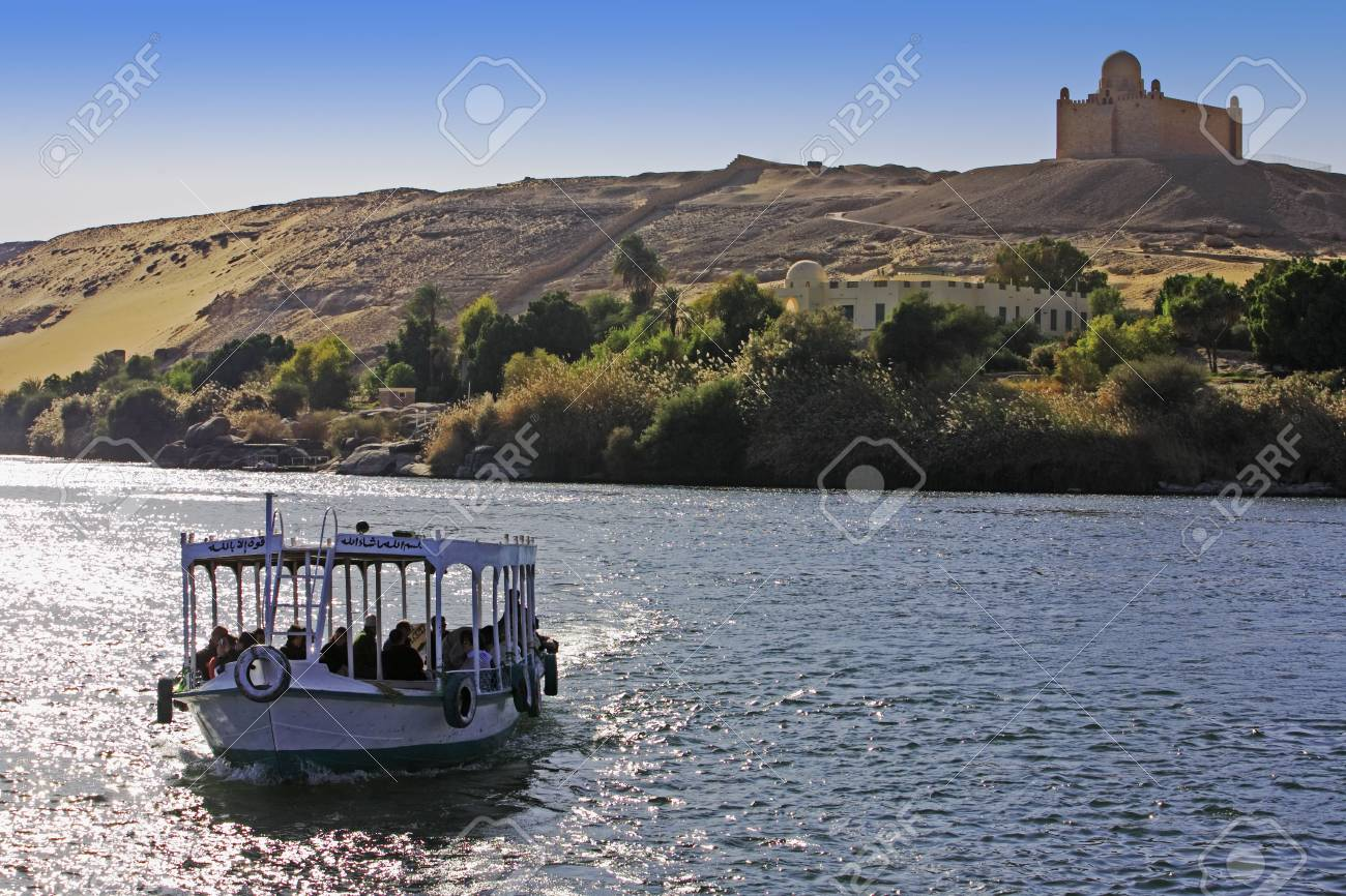 boat cruising on the river nile with Aga Khan tomb on the shore near aswan in egypt - 121743487