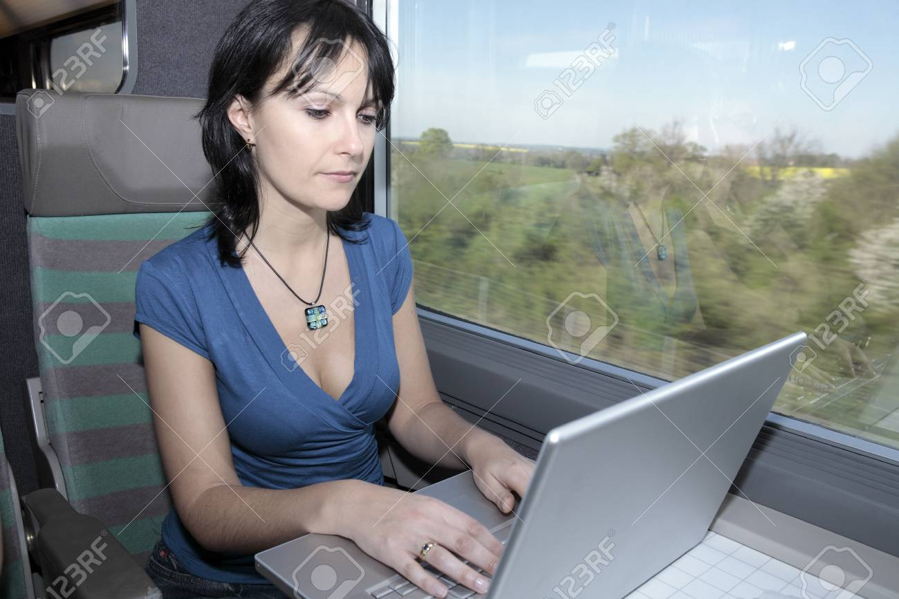 beautiful young woman woman in a train using a computer lap top - 121743605