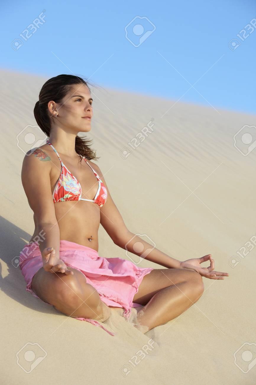 beautiful smiling bikini dressed young brazilian woman medtating on the sand dune of jericoacoara ceara state near fortaleza - 121743618