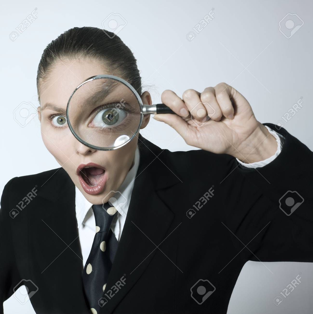 studio shot portrait of a beautiful young woman in a costume suit looking through magnifying glas Stock Photo - 2966666