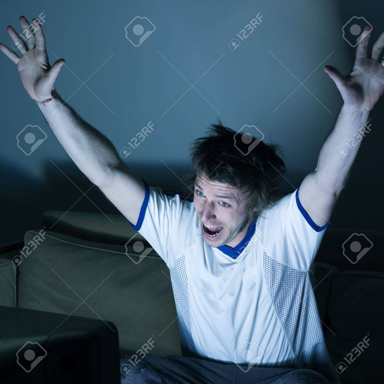 pictures in a living room a funny and expressive man sitting on a couch  watching on tv  sport event Stock Photo - 2966810