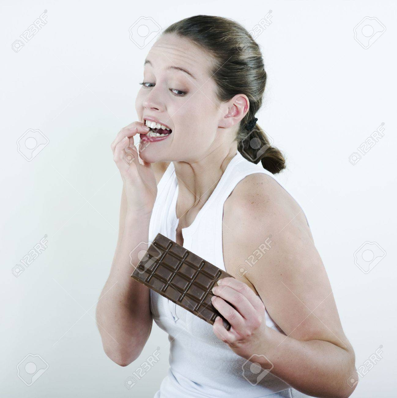 studio portrait on isolated background of a young beautiful caucasian woman holding a chocolate table Stock Photo - 2966828
