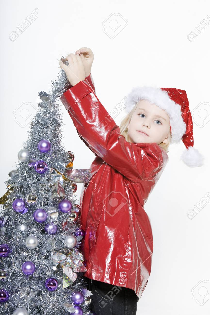 indoors picture of a little girl preparing christmas tree on isolated white background Stock Photo - 3999755