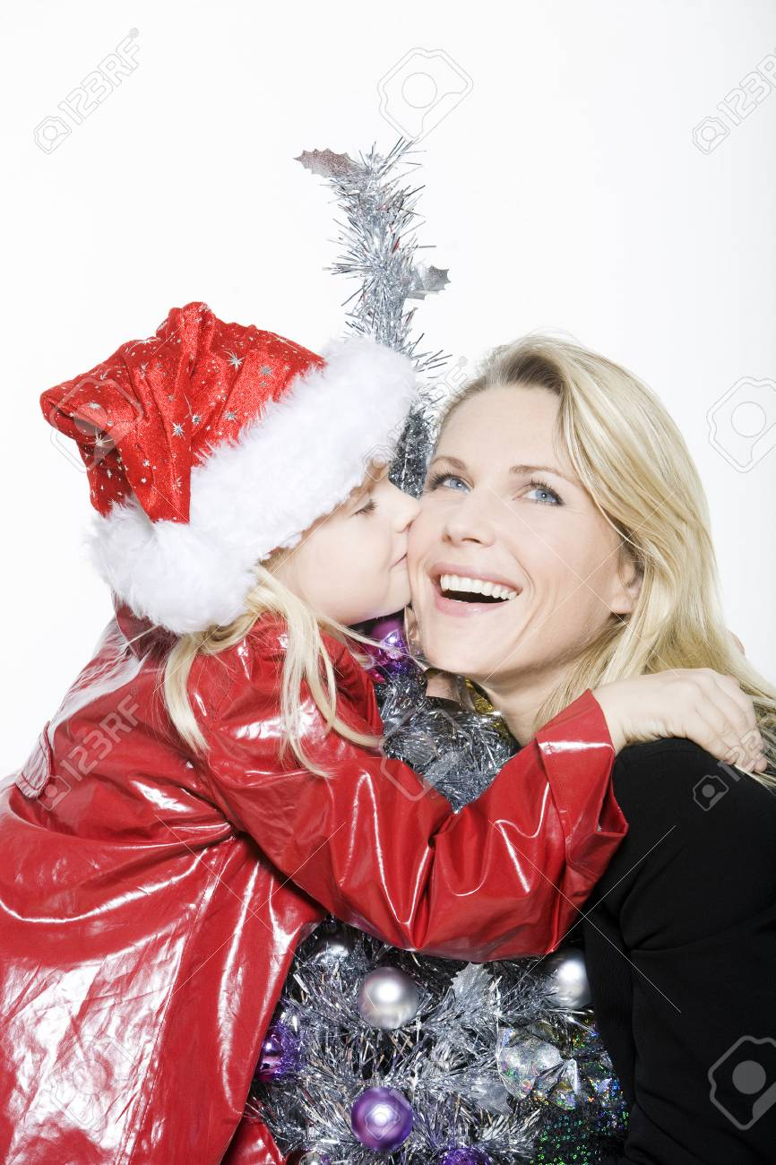 indoors picture of a little girl with her mother preparing christmas tree on isolated white background Stock Photo - 3999728