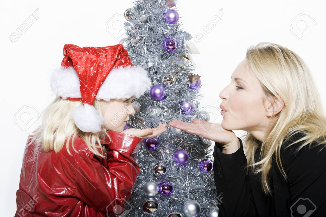 indoors picture of a little girl with her mother preparing christmas tree on isolated white background Stock Photo - 3999765