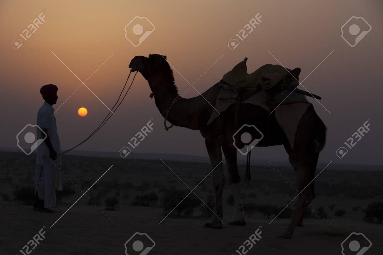 man looking at his camel during sunset khuri dunes in thar desert near jaisalmer in rajasthan state in india Stock Photo - 9800090