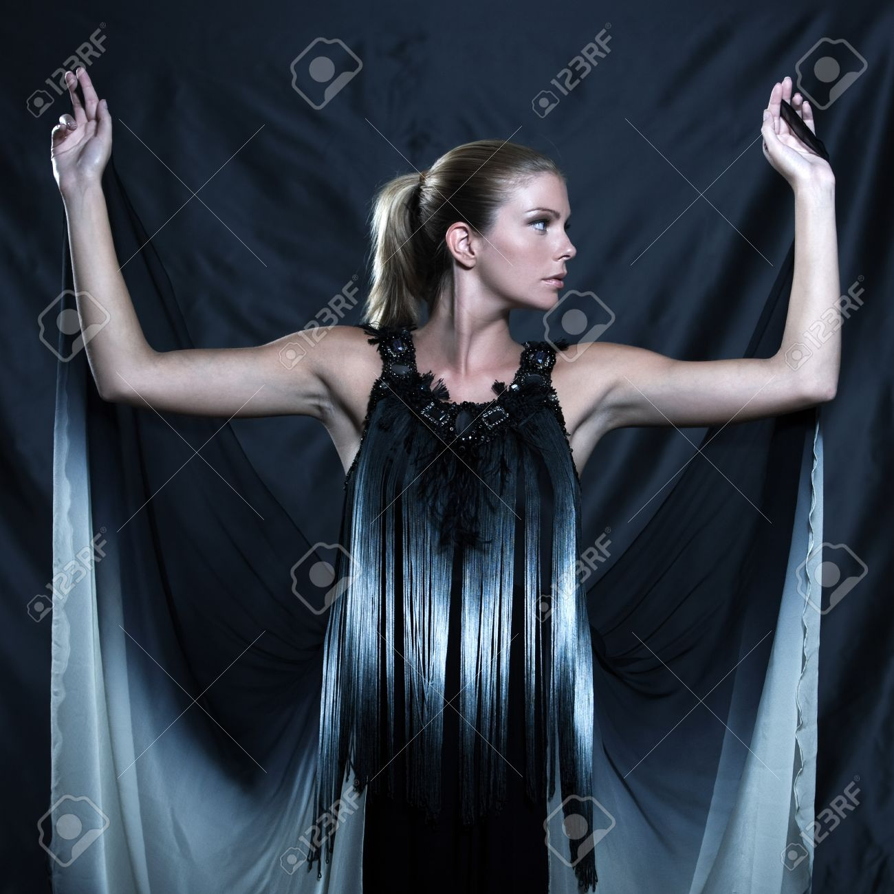 fashion pictures of a beautiful woman wearing silk fringe black and white dress chinese style doing martial arts posture Stock Photo - 9823626
