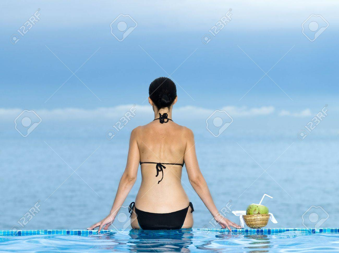 woman siiting on a the edge of a swimming pool looking at the se Stock Photo