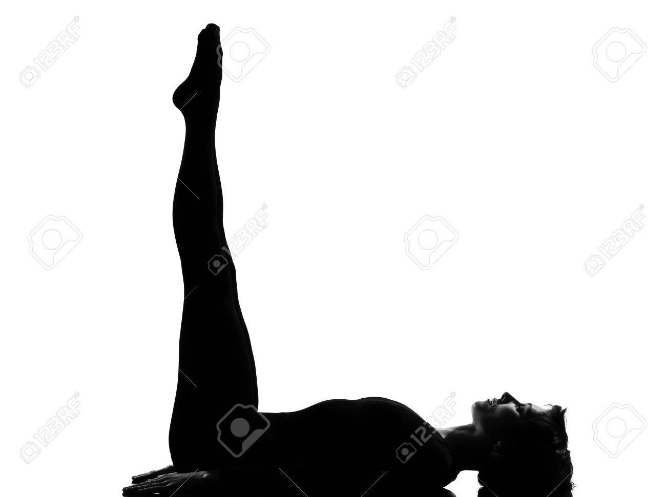 woman yoga Upward Extended Feet Pose - urdhva prasarita padasana exercising lying on back fitness yoga stretching  in shadow grayscale silhouette full length in studio isolated white background Stock Photo - 9799784