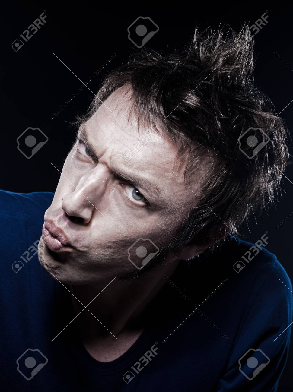 studio portrait on black background of a funny expressive caucasian man pucker strain Stock Photo - 11635338