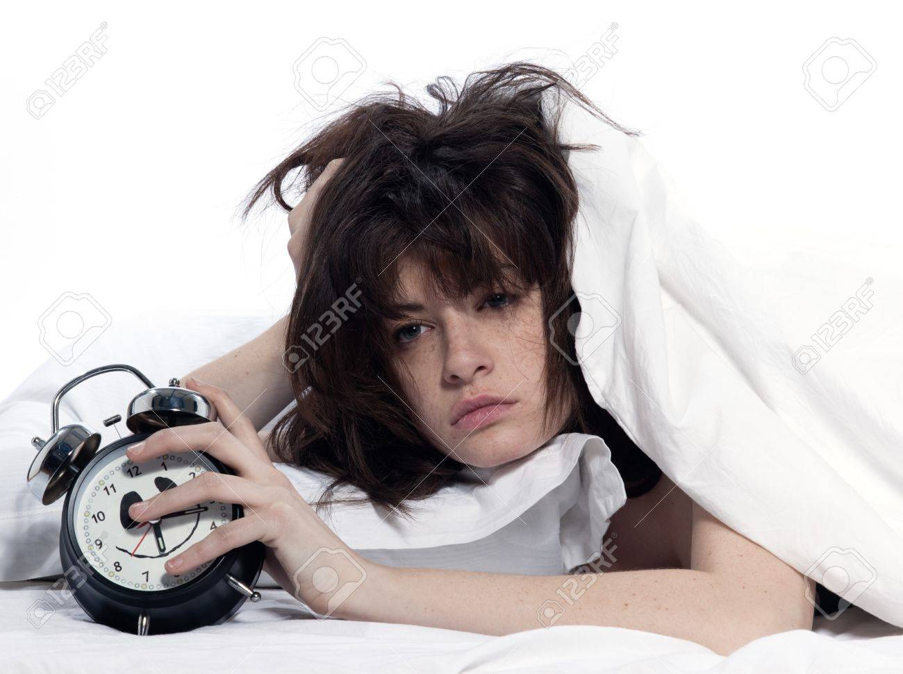young woman woman in bed awakening tired holding alarm clock on white background - 11752815