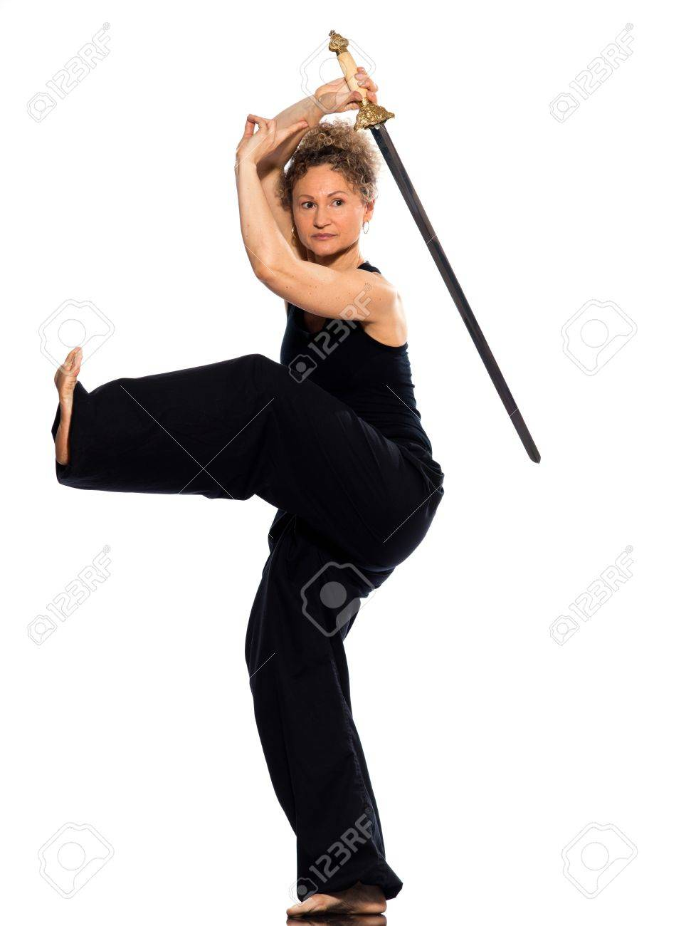 mature woman praticing tai chi chuan with sword in studio on isolated white background Stock Photo - 11766399