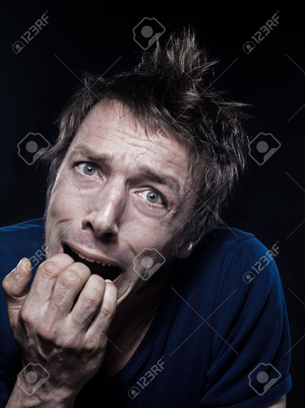 studio portrait on black background of a funny expressive caucasian man grimacing fear - 12710836