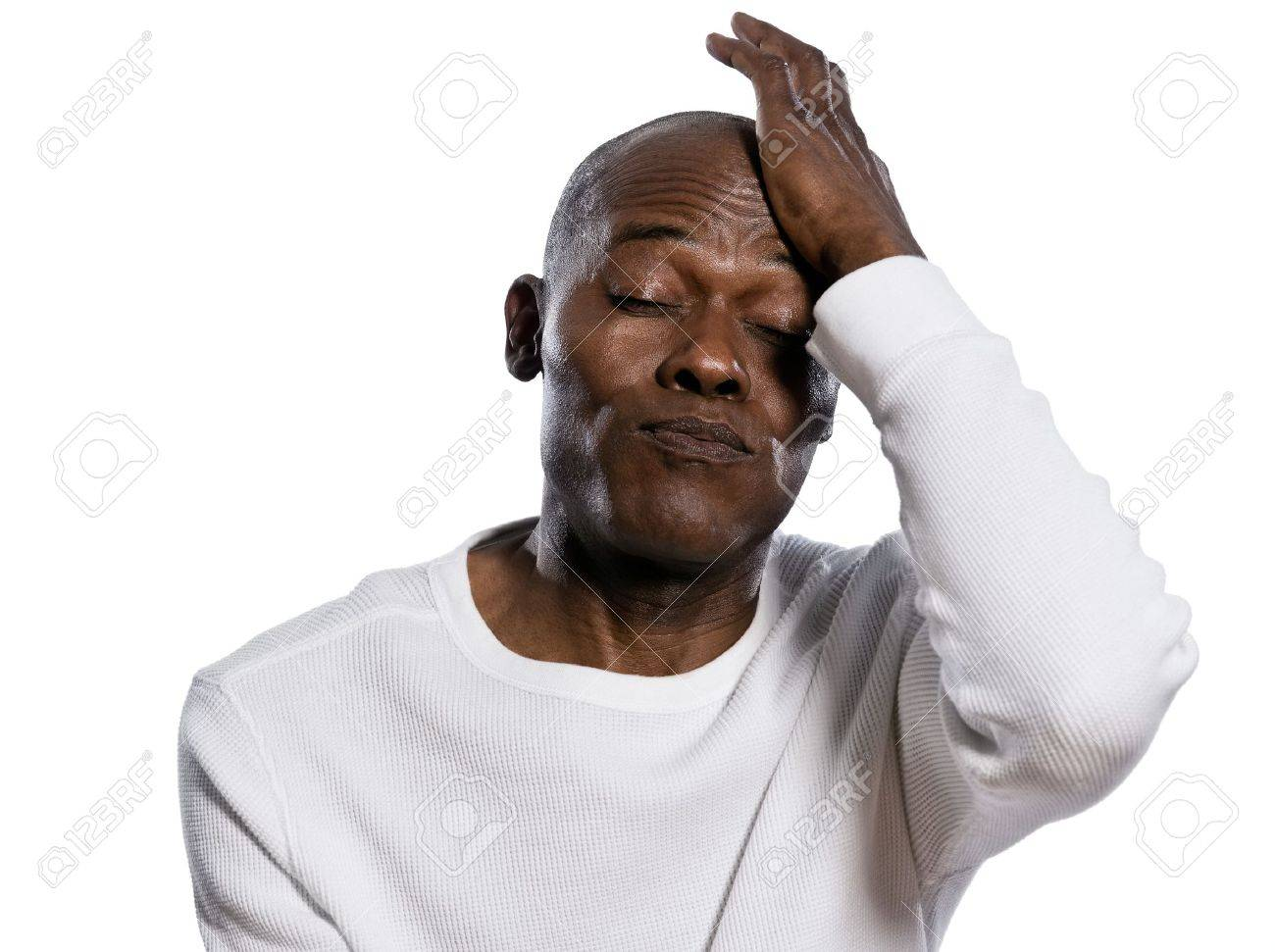 Close-up of a displeased afro American man with hand on head puffing in studio on white isolated background Stock Photo - 14683243