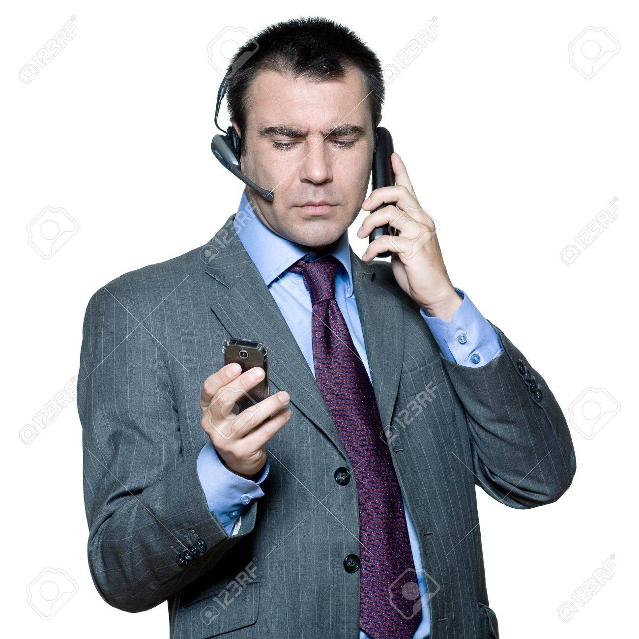 Portrait of businessman wearing headset and using mobile phone busy with multiple telephone in studio isolated white background Stock Photo - 15641604