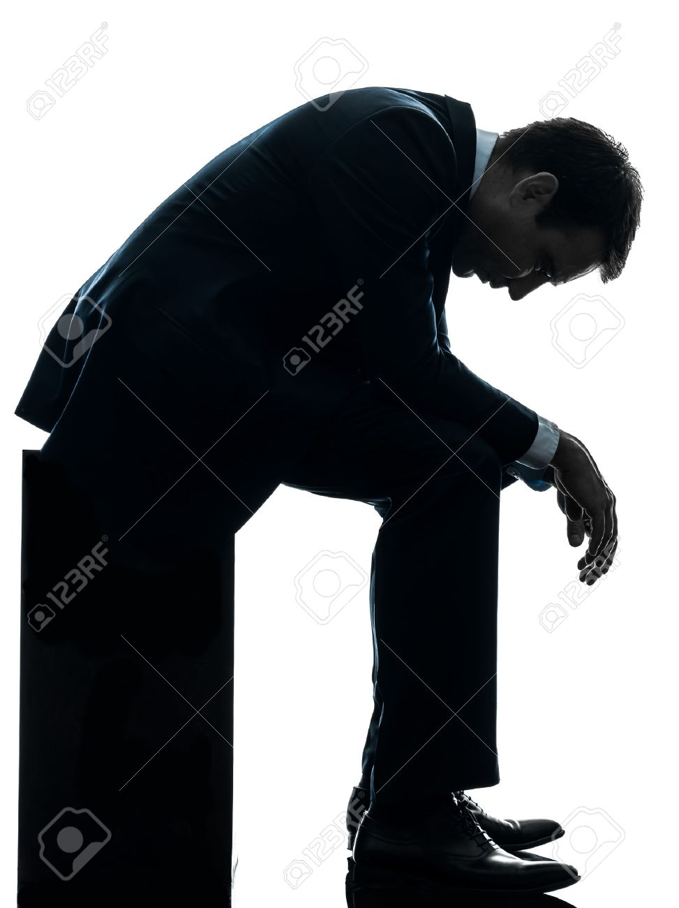 one caucasian sad business man  sitting pensive looking down  in silhouette studio isolated on white background Stock Photo - 17798221