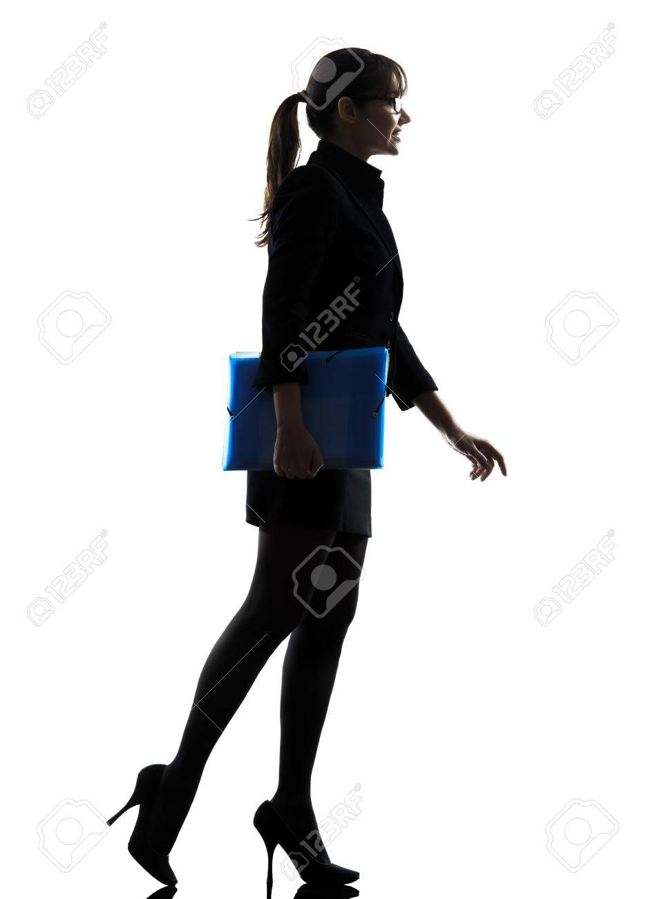 one caucasian business business woman  holding folders files walking silhouette in silhouette studio isolated on white background Stock Photo - 18632800