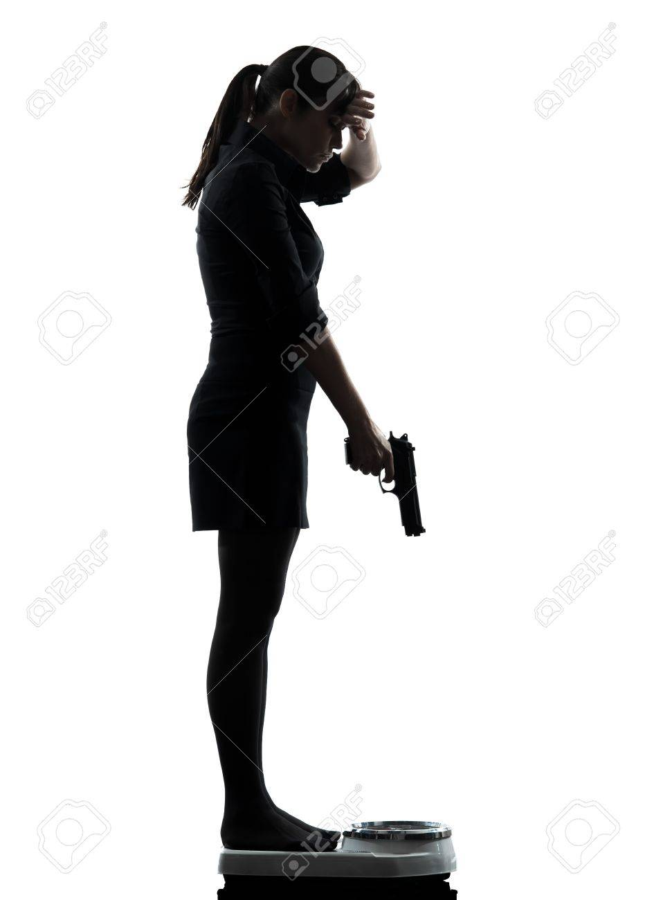 one woman standing on weight scale despair aiming gun silhouette studio isolated on white background Stock Photo - 18838099