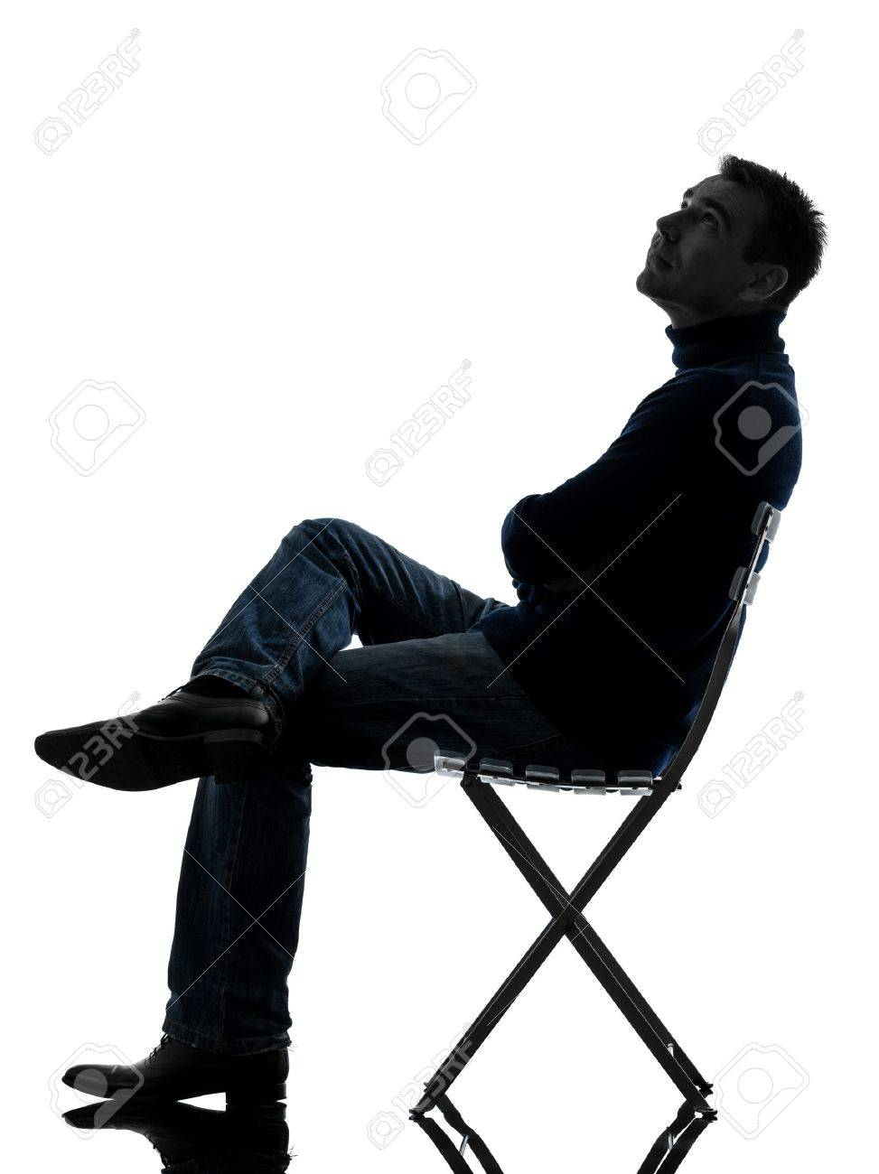 Man sitting in chair side - One Caucasian Man Sitting Looking Up Full Length In Silhouette Studio Isolated On White Background Stock
