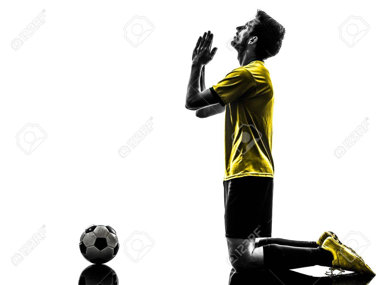 one brazilian soccer football player young man praying in silhouette studio  on white background Stock Photo - 20726403