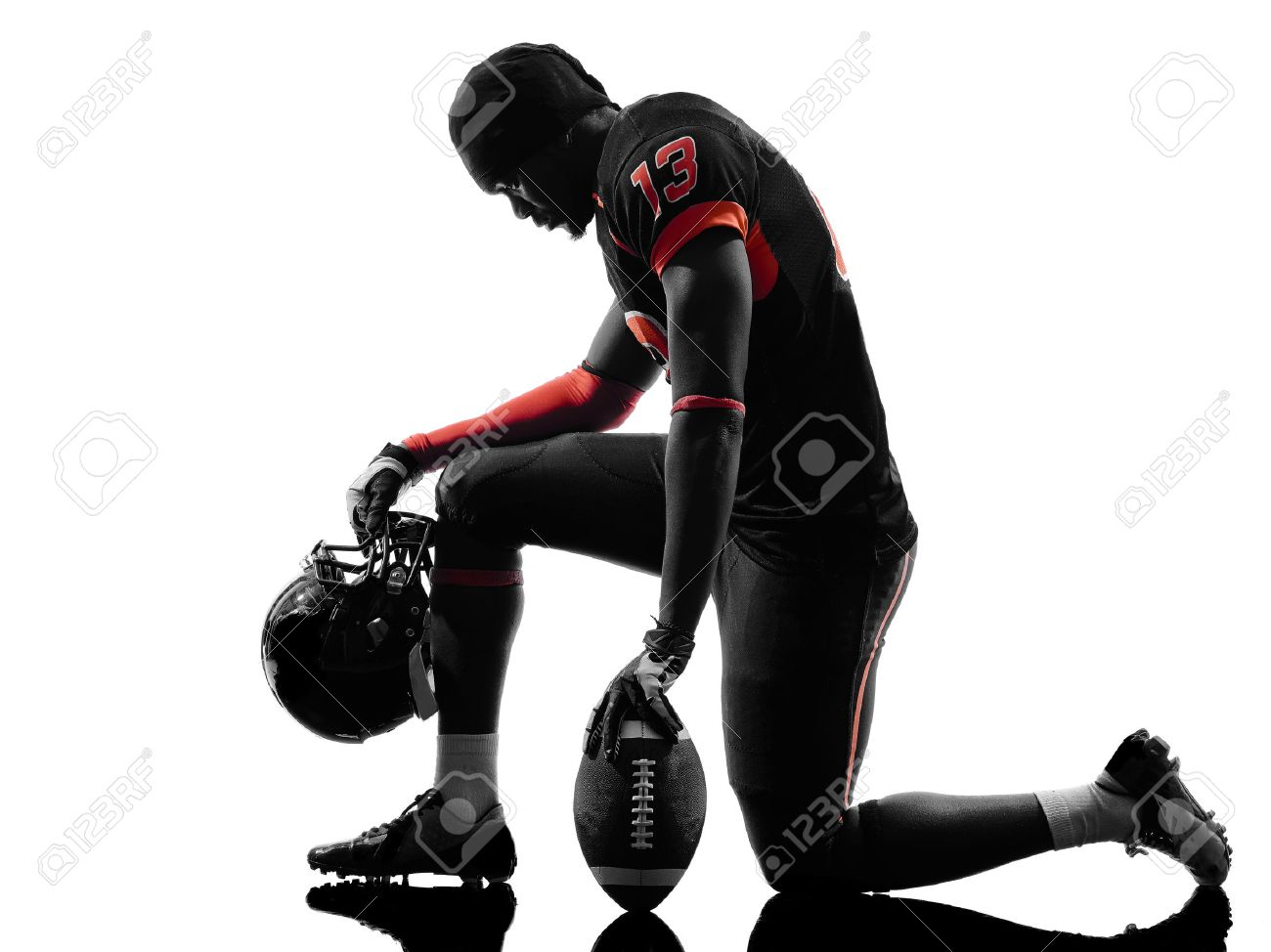 one american football player kneeling in silhouette shadow on white background stock photo 23309117