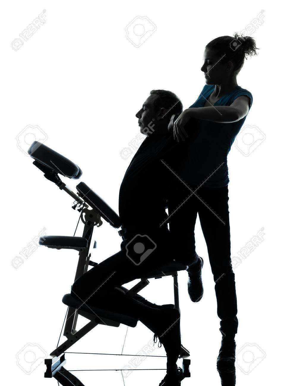Chair massage therapy - One Man And Woman Performing Chair Back Massage In Silhouette Studio On White Background Stock Photo