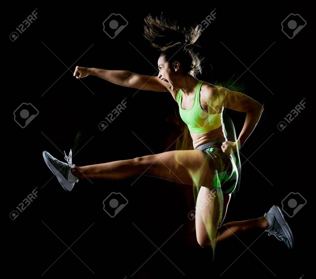 one mixed race woman exercising fitness exercises isolated on black background with lightpainting effect - 120854649