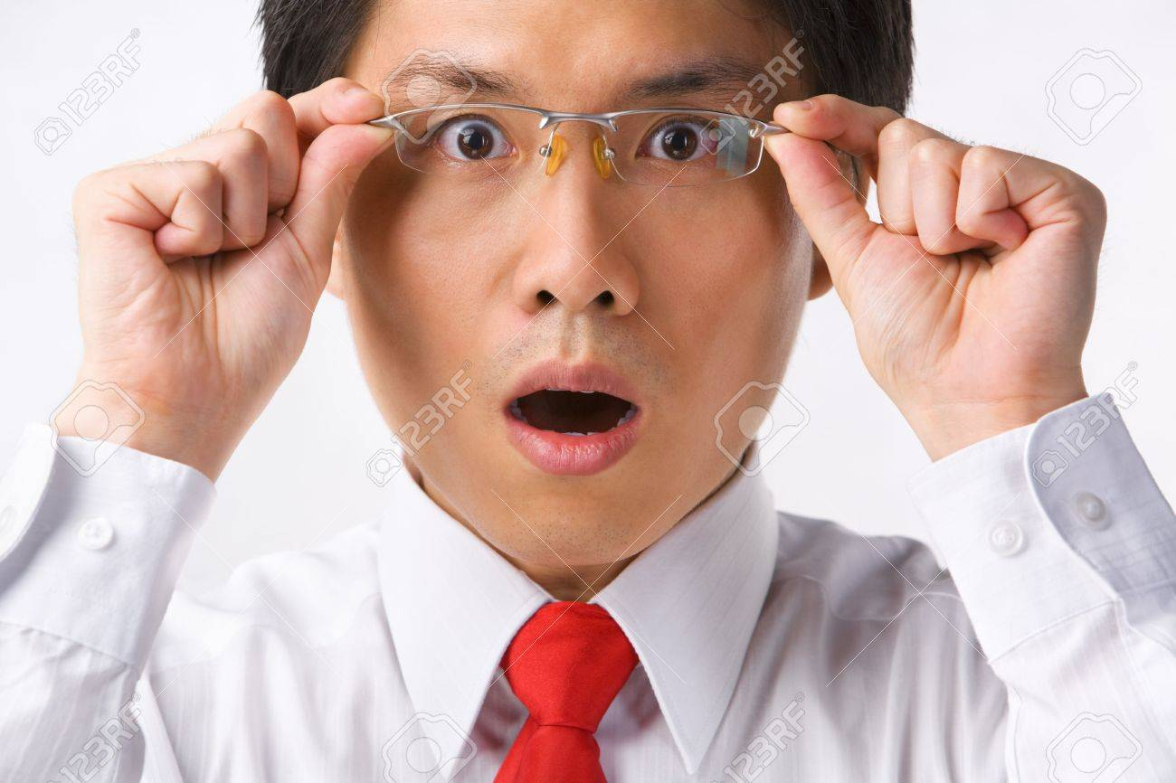 A young Asian businessman gazing at camera while holding glasses to camera with surprised expression Stock Photo - 5128060