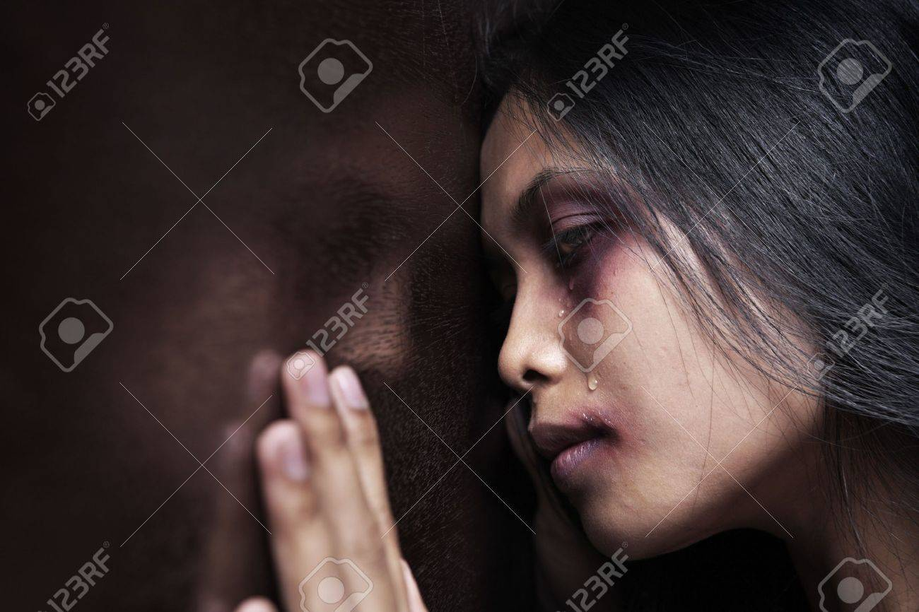 Injured woman leaning sadly on wooden wall, concept for domestic violence Stock Photo - 6612051