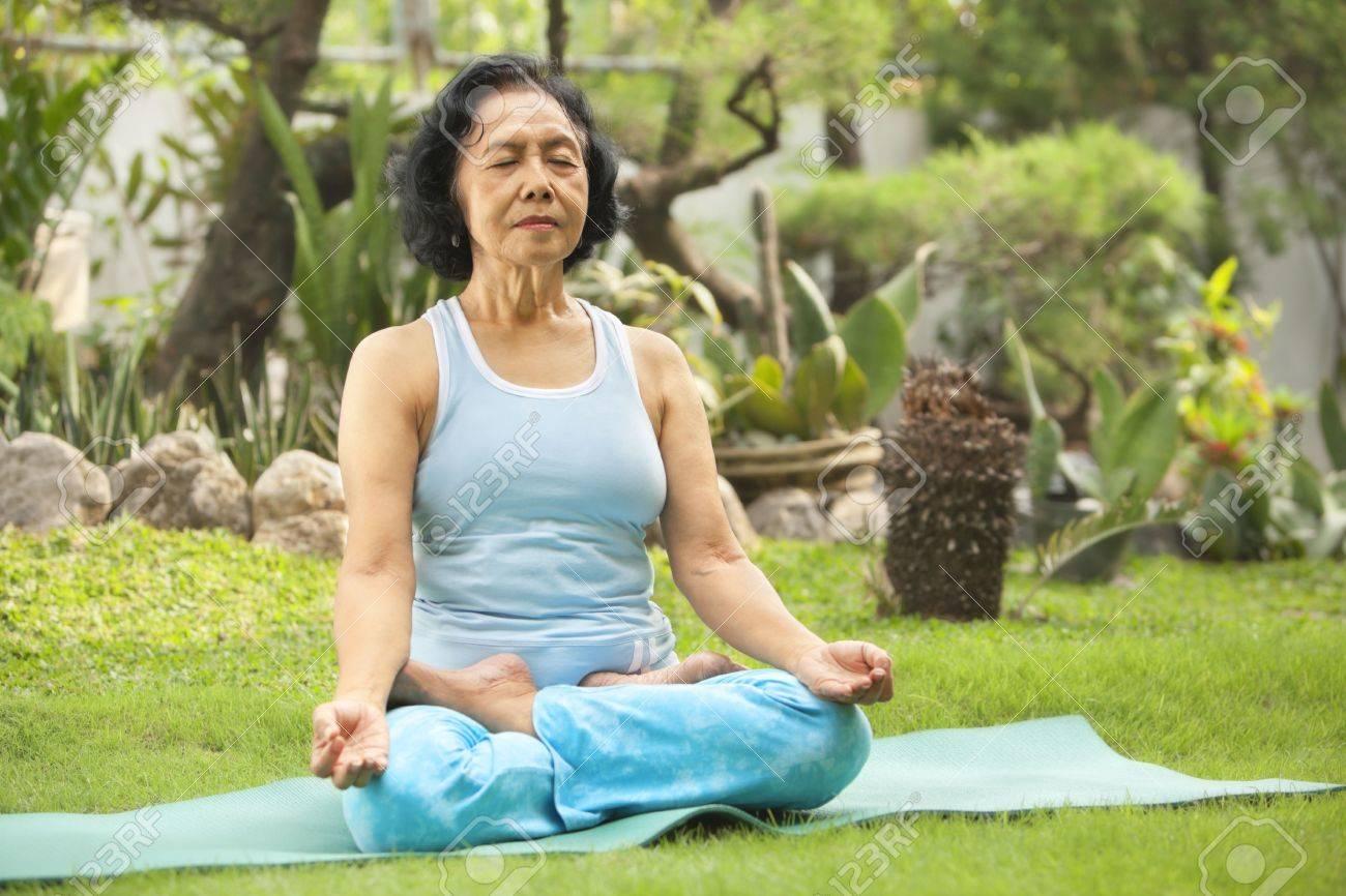 Asian senior woman meditating for yoga outside, green plant as background Stock Photo - 6264366