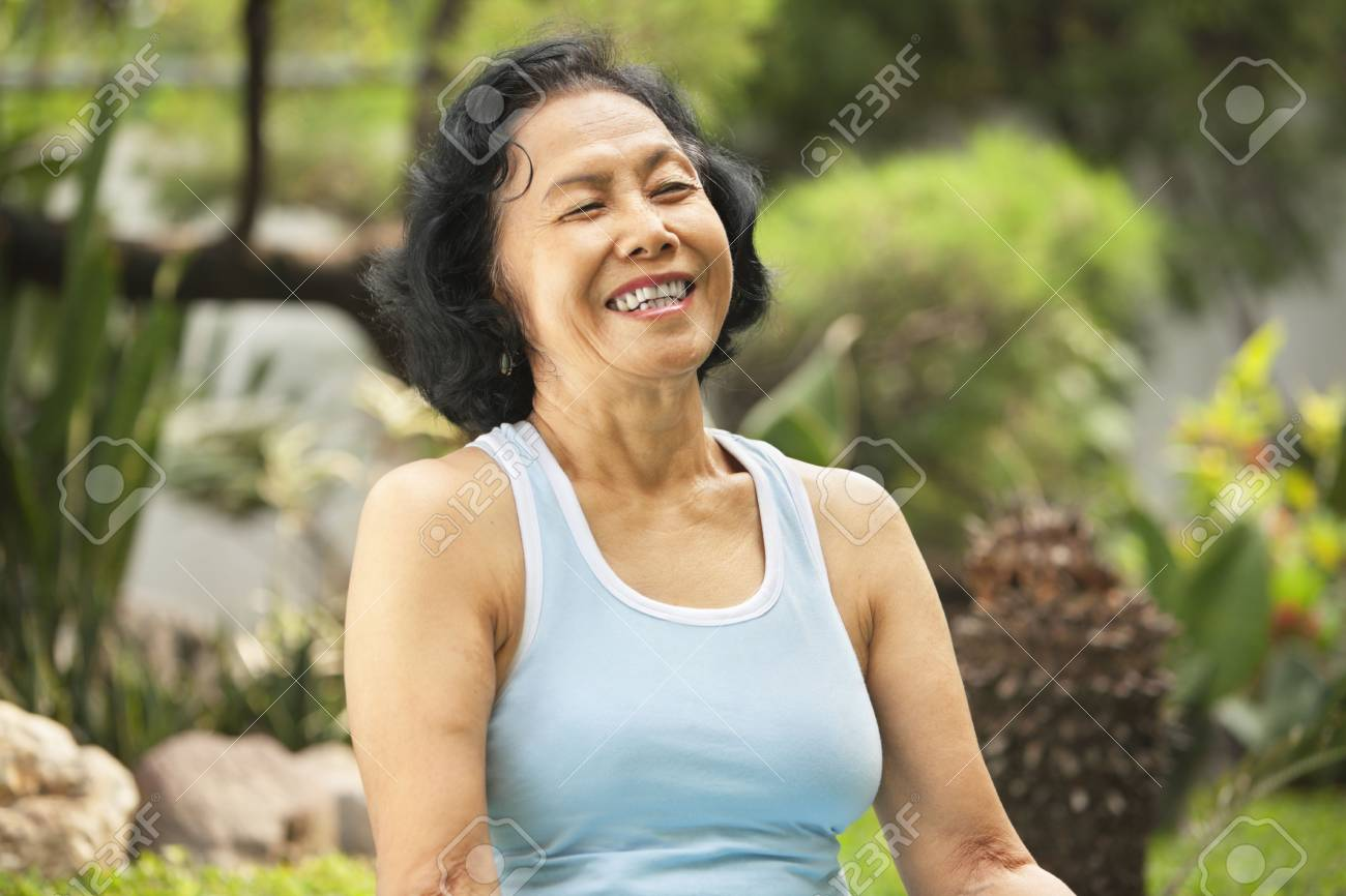 Senior Asian woman laught at park after yoga training Stock Photo - 6264321
