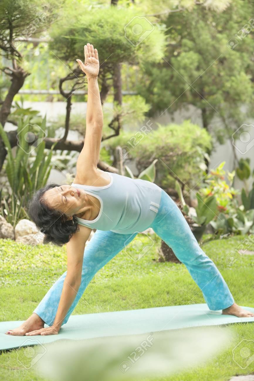 Senior Asian woman doing strecthing for yoga in garden Stock Photo - 6264367