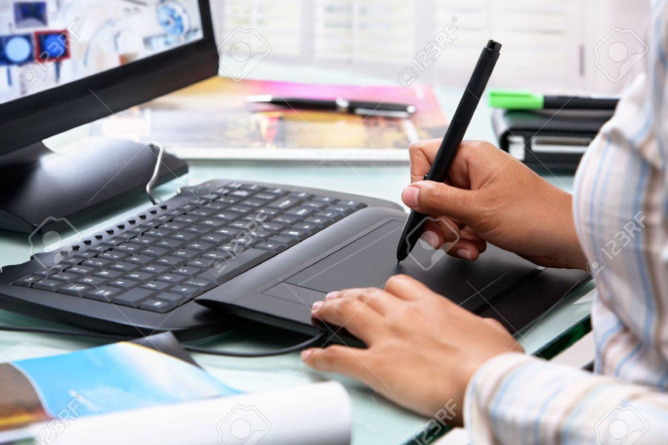 Female graphic designer working in office using tablet pen, selective focus Stock Photo - 6525461