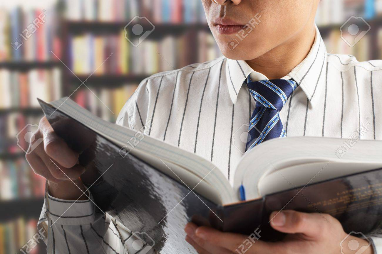 Unrecognizable businessman or professor reading journal to search for data in library Standard-Bild - 7283407