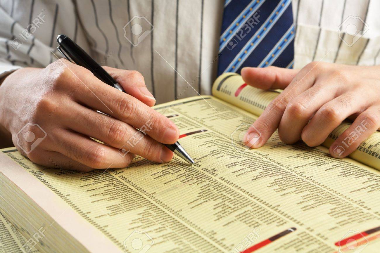 Businessman searching for something in yellow pages through indexes Stock Photo - 7284623