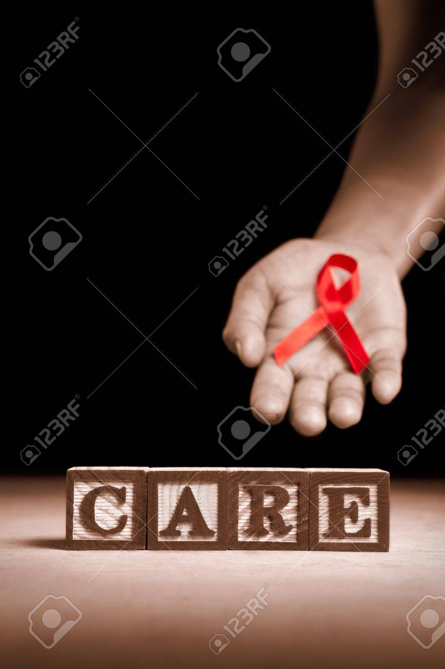 Word 'Care' from wooden block with hand holding red ribbon on dark background Stock Photo - 7988135