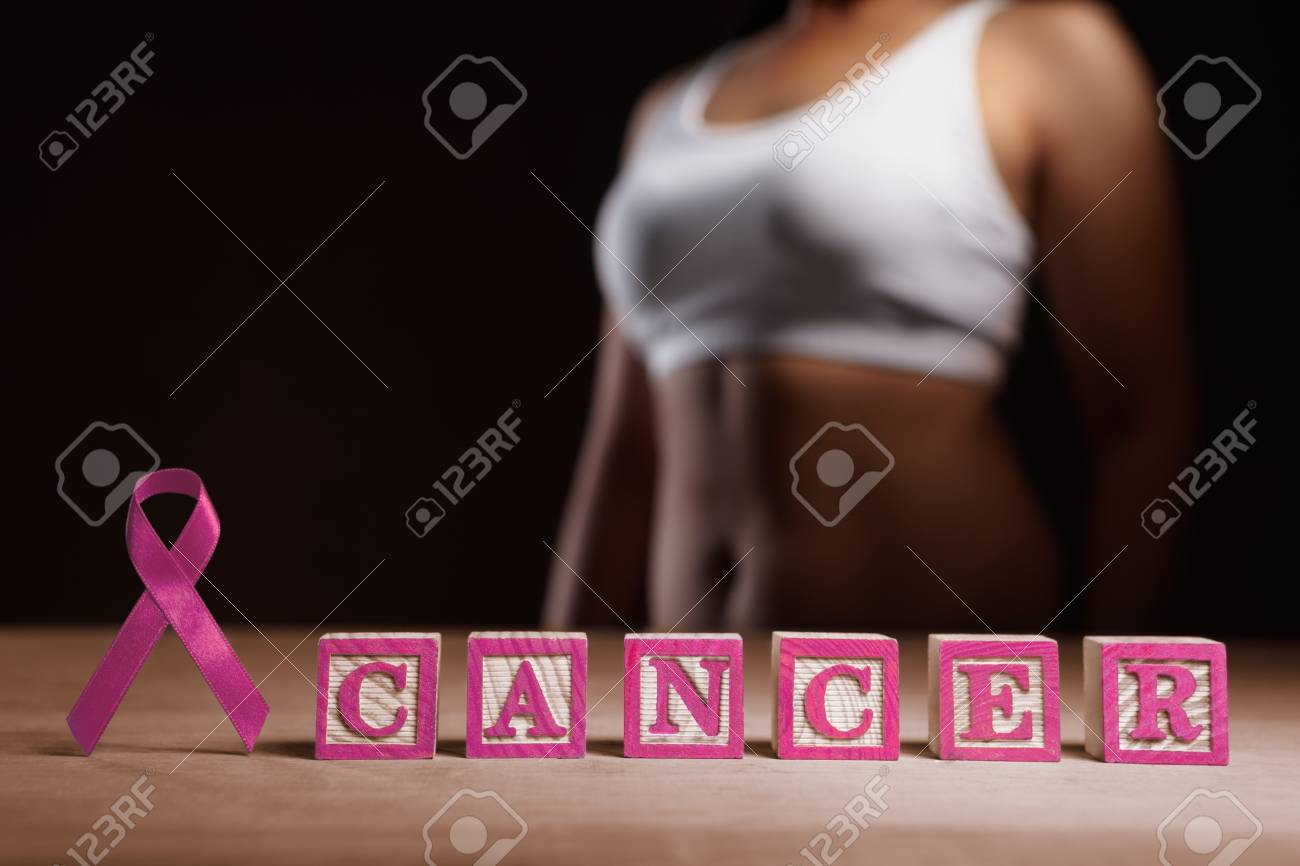 Pink ribbon and pink word 'CANCER' in front of woman's body Stock Photo - 7988256
