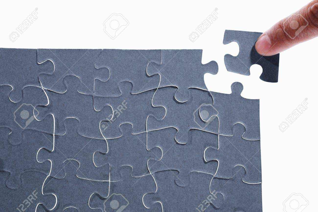 Finger putting the last piece of puzzle Stock Photo - 8875855