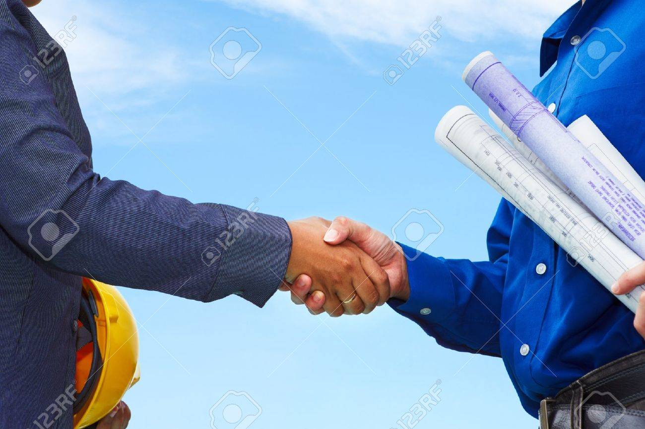 Two contractors shake hands with blue sky background - 10010318