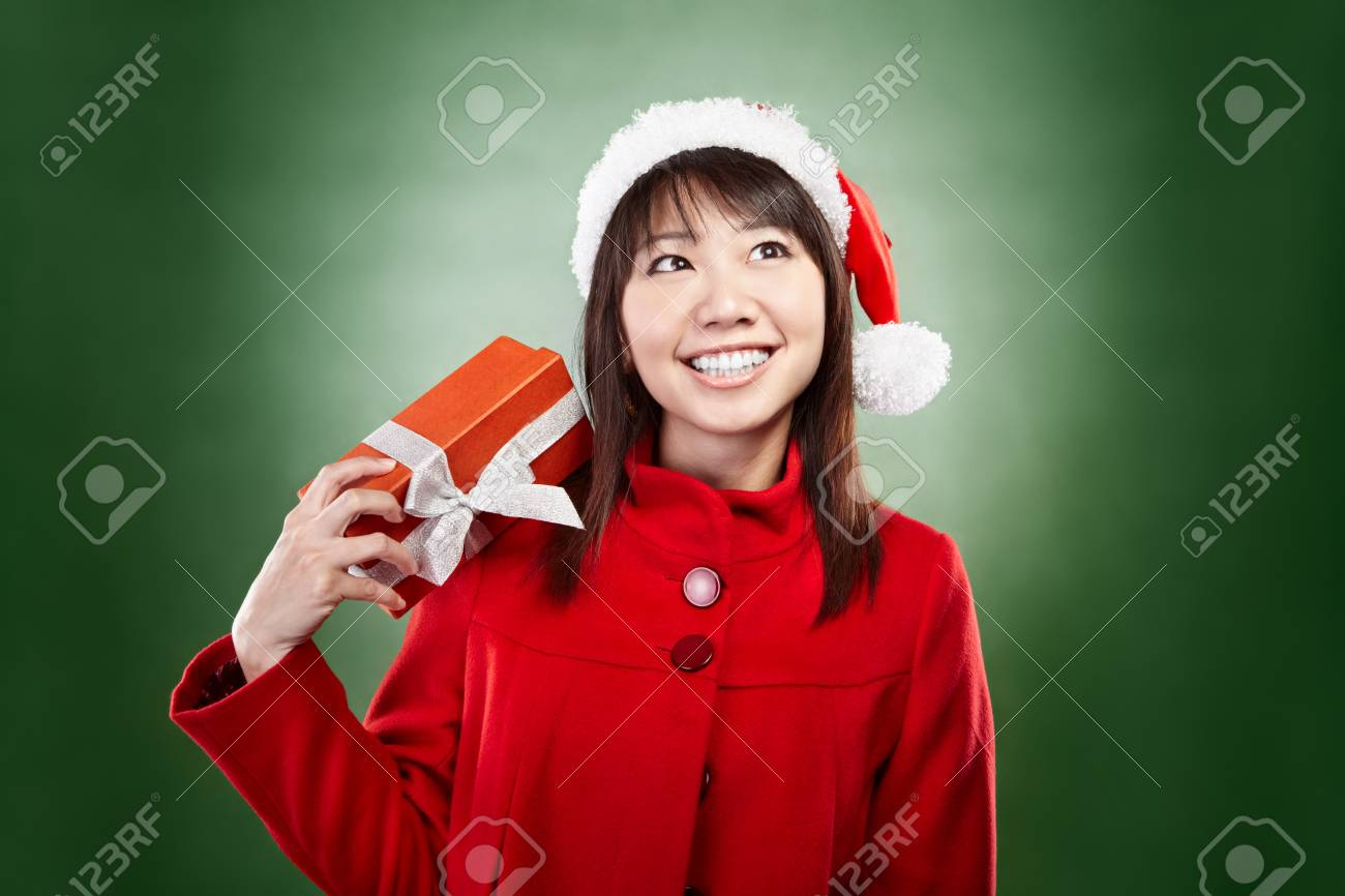 Asian lady with red Christmas outfit holding a present Stock Photo - 11492738