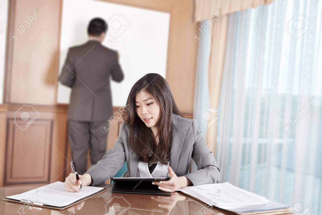 Chinese businesswoman busy working with her tablet while businessman on background busy preparing presentation Stock Photo - 12751244
